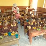A-Food-Vendor-assisting-one-of-the-pupils-to-peel-the-Banana-served-during-mid-day-meal1