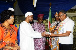 Brazilian Representative of Obafemi Awolowo University (OAU), Ile-Ife in the Afro-Identity International Conference, Sir Joe Monteiro, presenting a bulk of Compact Disc to the Governor, State of Osun, Ogbeni Rauf Aregbesola, during a get-together dinner party organized by the Governor, marking the O.A.U & Afro-Identity International Conference while the Deputy Governor, State of Osun, Mrs Titi Laoye-Tomori [left], State of Osun, Head of Service, Mr. Sunday Owoeye [middle] and Dr. Felix Omidire [ second right] watch at the State Government House, Osogbo on 26/08/2013