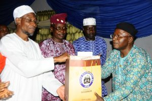 Governor, State of Osun, Ogbeni Rauf Aregbesola presenting a gift to the former Dean, Faculty of Arts, Obafemi Awolowo University (OAU), Ile-Ife, Professor Dipo Salami while State of Osun, Head of Service, Mr. Sunday Owoeye and commissioner for Home Affairs, Tourism and Culture, Mr. Sikiru Ayedun look during a get-together dinner party organized by the Governo,r marking the O.A.U & Afro-Identity International Conference at the State Government House, Osogbo on 26/08/201