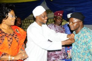 Governor, State of Osun, Ogbeni Rauf Aregbesola, decorating the former Dean, Faculty of Arts, Obafemi Awolowo University (OAU), Ile-Ife, Professor Dipo Salami while the Deputy Governor, State of Osun, Otunba Titi Laoye-Tomori [left] and the State of Osun, Head of Service, Mr. Sunday Owoeye looks on, during a get-together dinner party organized by the Governor, marking the O.A.U & Afro-Identity International Conference at the State Government House, Osogbo on 26/08/2013