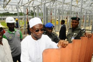Governor State of Osun, Ogbeni Rauf Aregbesola, checking the quality of the iron sheets of the on-going fabricated school building, during his impromptu visit at Saint Stephen Elementary Model School, Ode-Omu, State of Osun on Thursday