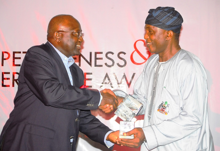 Secretary to the State Government of Osun, Alhaji Moshood Adeoti (right) representing the Governor, receiving an Award as the Best Governor in Youth and Sports Development from Chairman Tanus Communications limited, Mr Yemi Ogunbiyi, during the Businessday States Competitiveness and Good Governance Awards 2013, at Federal Palace Hotel Victoria Island, Lagos State on Wednesday 13-11-2013