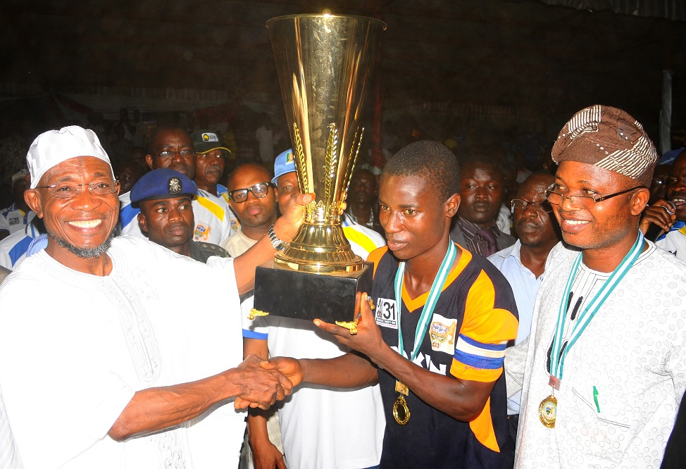 Governor State of Osun, Ogbeni Rauf Aregbesola (left) presenting the State of Osun Under-17 Governor's Cup to the Captain Obokun Local Government team, Adebayo Jelili after defeating their counterpart from Orolu LG, at technical college, Osogbo the State of Osun. With them is, Chairman Obokun Local Government, Dr Gbenga Ogunleye.