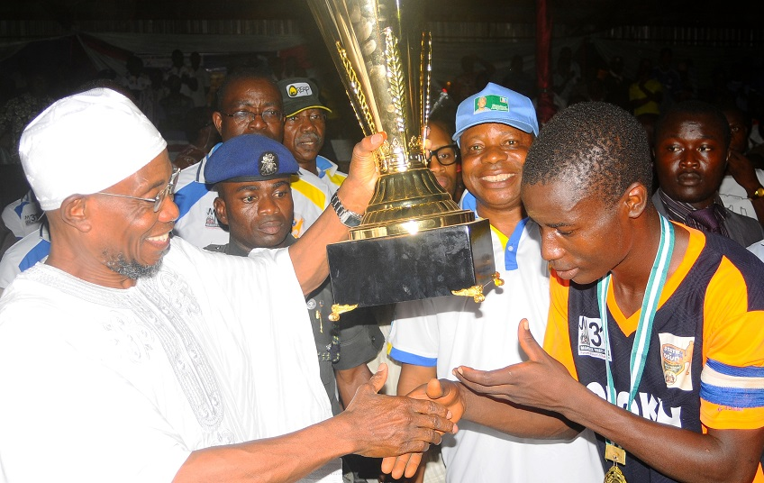 Governor State of Osun, Ogbeni Rauf Aregbesola (left) presenting the State of Osun Under-17 Governor's Cup to the Captain Obokun Local Government team, Adebayo Jeleel after defeating their counterpart from Orolu LG, at technical college, Osogbo the State of Osun. With them is, Special Adviser to the Governor on Youth, Sports and Special needs, Comrade Biyi Odunlade.