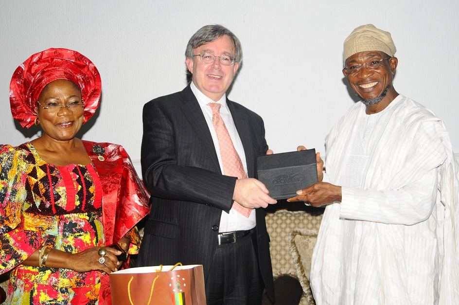 Governor State of Osun, Ogbeni Rauf Aregbesola, presenting 'Tablet of Knowledge: Opon Imo' to the British Deputy High Commissioner, Peter Carter. With them is, Deputy Governor, Mrs Titi Laoye-Tomori, during a reception for the Deputy High Commissioner on his visit to the State, at Government House, Osogbo, State of Osun on Wednesday 11-12-2013