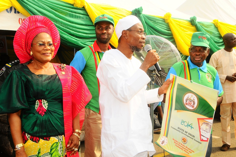 State of Osun Chairman, Community Development Council, Chief Michael Okediya (right) Presenting a Plague to the Governor State of Osun, Ogbeni Rauf Aregbesola after his Investiture as Grand Patron of the Council and Support for his second term in office, at Nelson Mandela Freedom Park, Osogbo, State of Osun. With them are, Deputy Governor, Mrs Titi Laoye-Tomori and Special Adviser to the Governor on Rural Development and Community Affairs, Mr Kunle Ige (3rd left) on Tuesday