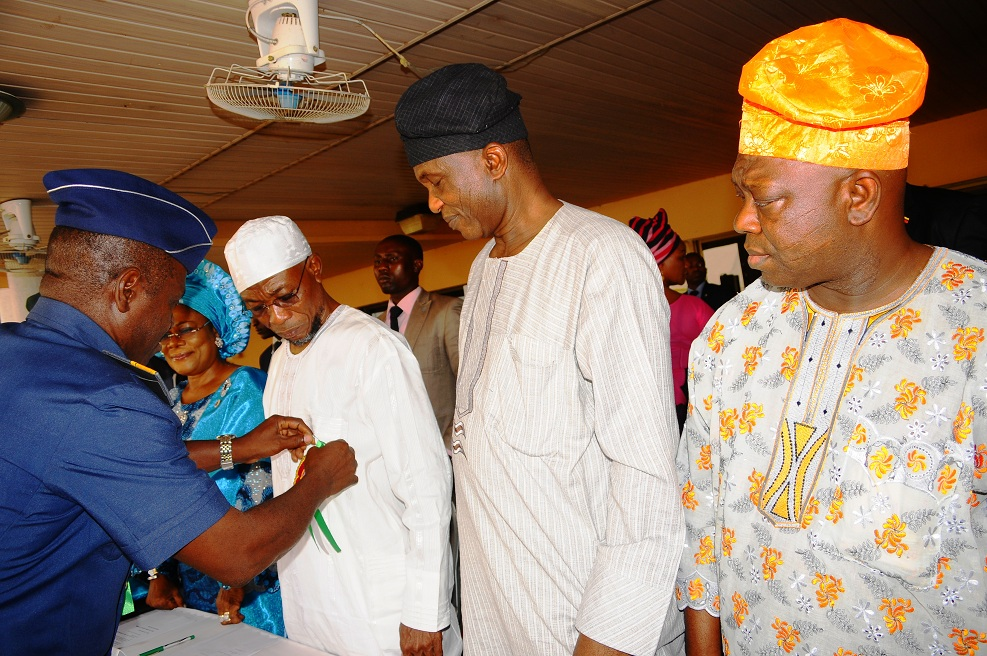 Governor State of Osun, Ogbeni Rauf Aregbesola (3rd left) being decorated with Emblem for Year 2014 Armed Forces Remembrance Day Celebration by the Commandant, Air Force Safety Institute, Ipetu-Ijesa, Air Vice Marshal Christopher Gudi (left). With them are, Deputy Governor, Mrs Titi Laoye-Tomori (2nd left); Secretary to the State Government, Alhaji Moshood Adeoti (2nd right) and Deputy Speaker, State House of Assembly of Osun, Honourable Akintunde Adegboye (right), at Government House, Osogbo, State of Osun on Thursday 09-01-2014