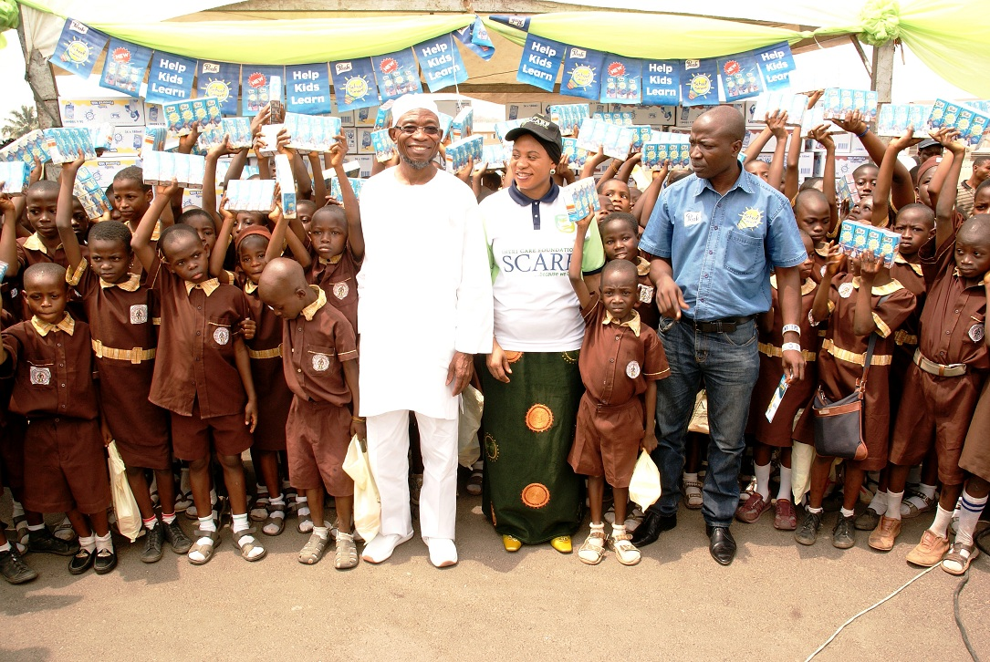 Governor, State of Osun, Ogbeni Rauf Aregbesola; his Wife, Sherifat; and Managing Director, Peak School Smart, Mr Ezekiel Salami flanked by Pupils in Public Elementary Schools in the State, during the Distribution of Sheri Care Foundation (SCARF) Milk of Knowledge to the Pupils at Nelson Mandela Freedom Park, Osogbo, State of Osun on Thursday 20-02-2014