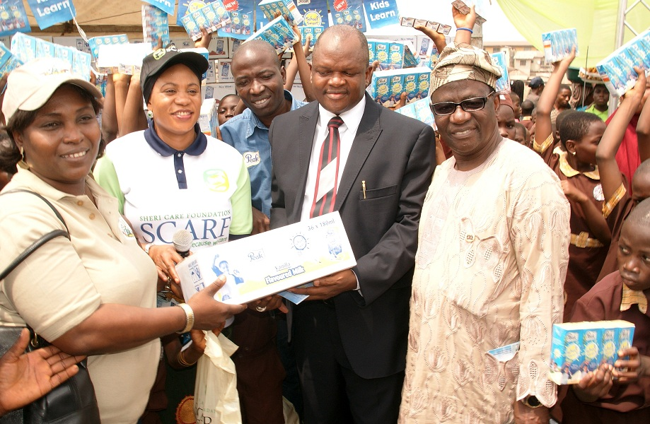 "Wife of the Governor, State of Osun, Mrs Sherifat Aregbesola presenting the Sheri Care Foundation (SCARF) Milk of Knowledge to the Permanent Secretary, State Universal Basic Education Board (SUBEB), Alhaji Fatai Kolawole (2nd right); Chairman, State Universal Basic Education Board (SUBEB), Prince Felix Awofisayo (right) and Director, Osun School Feeding Programme tagged: ""O-Meals"", Mrs Ayoola Olubunmi (left), during the Distribution of SCARF Milk of Knowledge to the Pupils in Public Elementary Schools in the State at Nelson Mandela Freedom Park, Osogbo, State of Osun on Thursday 20-02-2014"