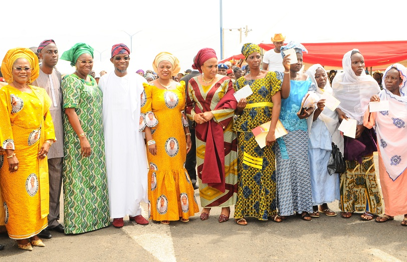 Governor State of Osun, Ogbeni Rauf Aregbesola (4th left); his wife, Sherifat (5th left); Deputy Governor, Mrs Titi Laoye-Tomori (left); wife of Lagos State Governor, Mrs Abimbola Fashola (3rd left); wife of Oyo State Governor, Mrs Florence Ajimobi (6th left); Executive Director, Grooming People for Better Livelihood Centre, Mr Adesoji Tayo (2nd left) and some beneficiaries with their cheques, during the official launching of Osun/Grooming Assisted Women Empowerment Programme and Distribution of N600Million Micro Credit to 18,000 women beneficiaries, held at Mandela Freedom Park, Osogbo, State of Osun on Tuesday 30-04-2014