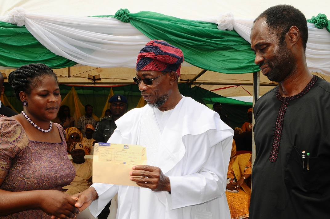 Governor State of Osun, Ogbeni Rauf Aregbesola, presenting cheque to one of the beneficiaries, Mrs Fausat Rasak from Olaruda Local Government. With them is Special Adviser to the Governor on Water Resources, Rural development and Community Affairs, Mr Kunle Ige, during the official launching of Osun/Grooming Assisted Women Empowerment Programme and Distribution of N600Million Micro Credit to 18,000 women beneficiaries, held at Mandela Freedom Park, Osogbo, State of Osun on Tuesday 30-04-2014