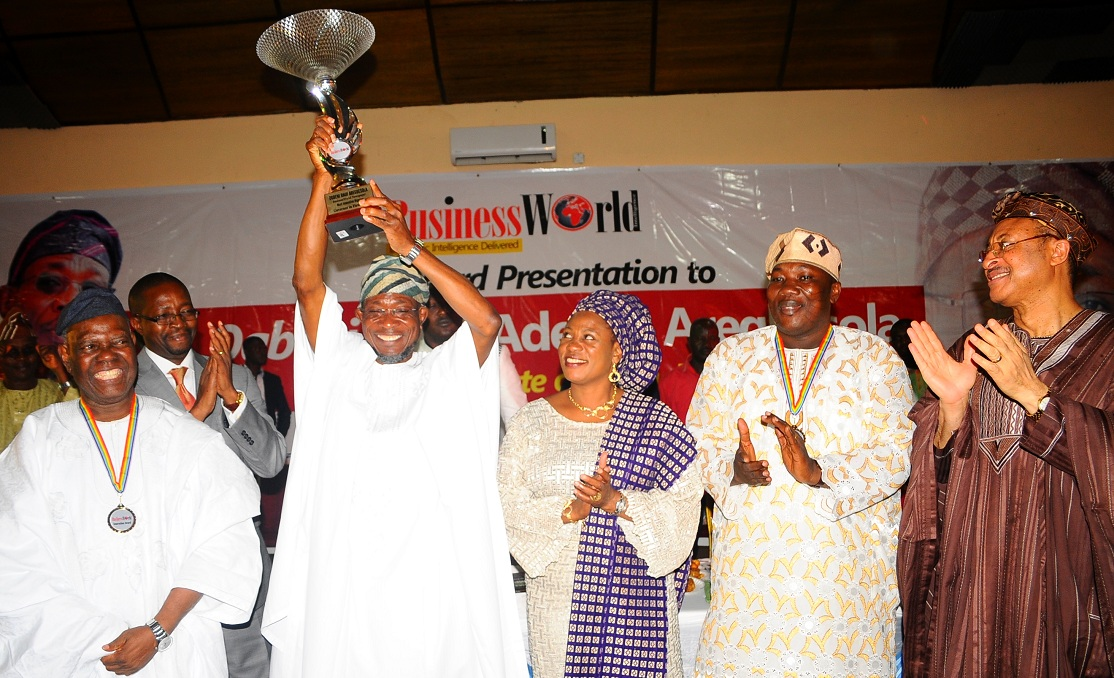 Governor State of Osun, Ogbeni Rauf Aregbesola (3rd left), displaying his BusinessWorld Newspaper Award as the Most Innovative Governor in his First Term Tenure, during the Award Presentation at Zenababs Hotels and Resort, Ilesa, State of Osun on Saturday 03-05-2014. With him are, Chairman of the Occasion/Interim National Chairman, All Progressives Congress (APC), Chief Bisi Akande (left), Wife of the Governor, Mrs Sherifat Aregbesola (3rd right); Chairman, BusinessWorld Newspaper, Mr Daisi Omidiji (2nd left); Speaker, State House of Assembly of Osun, Honourable Najeem Salam (2nd right) and Guest Speaker, Professor Pat Utomi (right).