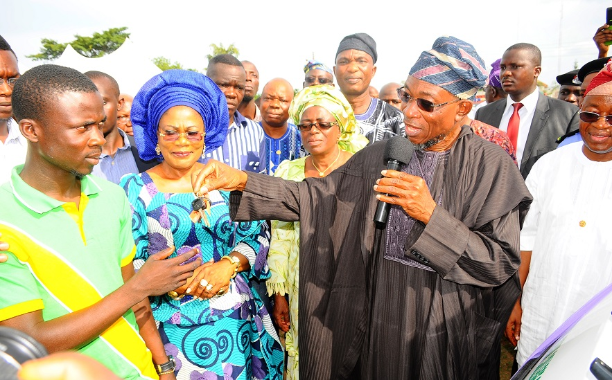 Governor State of Osun, Ogbeni Rauf Aregbesola (2nd right) Presenting an 18-seater Bus key to President, Student Union Government (SUG), Osun State College of Education, Ilesa, Comrade Elusakin Feranmi (left), during the Presentation of four 18-seater Buses to the SUG of the State-Owned Tertiary Institutions at Government House Lawn, Osogbo, State of Osun on Friday 02-05-2014. With them are, Deputy Governor, Mrs Titi Laoye-Tomori (2nd left); Special Adviser to the Governor on Tertiary Institutions, Alhaja Mulikat Bello (3rd left); Chief of Staff to the Governor, Alhaji Gboyega Oyetola (right) and others.