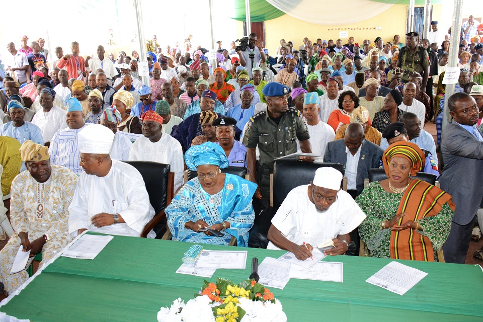 Governor State of Osun Ogben Rauf Aregbesola, signing copies of his Certificate of Return. With him are his wife, Sherifat (right); his Deputy, Mrs Titi Laoye-Tomori; former Executive Governor of the State, Senator Isiaka Adeleke (2nd left); Speaker of the House of Assembly, Hon. Najeem Salam and others, at the presentation of Certificate of Returns to Governor Aregbesola at INEC office, Osogbo, State of Osun on Tuesday 12-08-2014