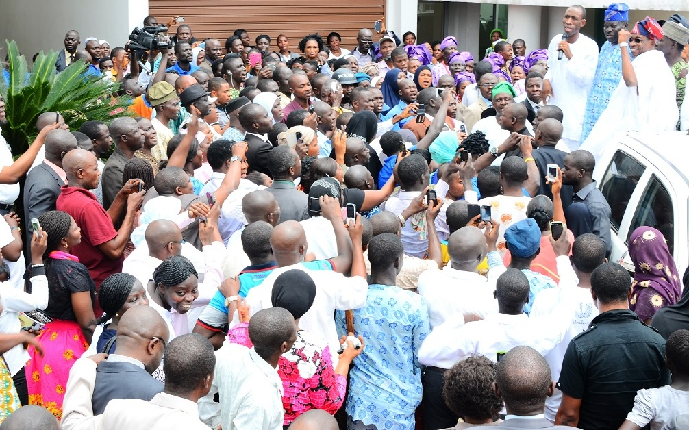 Governor State of Osun, Ogbeni Rauf Aregbesola (right) acknowledging cheers from Workers that trouped out en-mass to rejoice with him after his victory for second term in office, at Governor's office, Abere, State of Osun. With him are, Chairman, Nigeria Labour Congress, Osun Chapter, Comrade Saka Adesiyan (left); Chairman, Trade Union Congress, Comrade Francis Adetunji (middle); Chairman, Joint Negotiation Council, Comrade Bayo Adejumo (behind Aregbesola) and others, on Wednesday 10-09-2014.