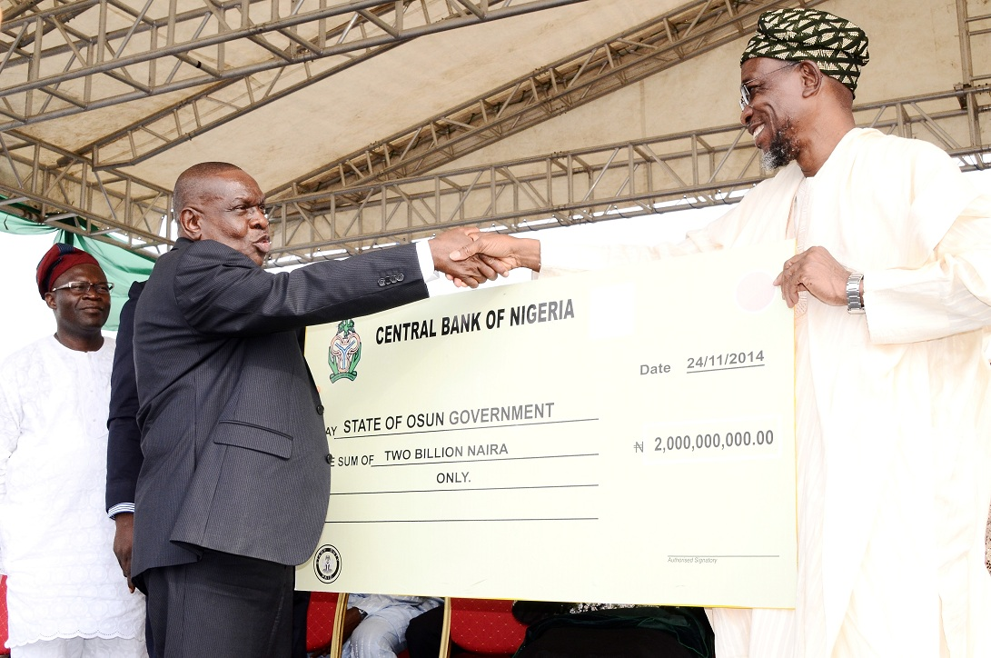 Governor State of Osun, Ogbeni Rauf Aregbesola (right) receiving Two Billion Naira Cheque from Special Adviser to Governor, Central Bank Nigeria (CBN) on Development Finance, Mr Paul Nduka (2nd left) and Commissioner for Commerce, Industry, Cooperatives and Empowerment, Mr Ismaila Alagbada (left), during the Disbursement of N2 Billion Accessed by the State to Loanees under the CBN N220 Billion Micro, Small and Medium Enterprises Development Fund at Nelson Mandela Freedom Park, Osogbo, State of Osun on Monday 24-11-2014