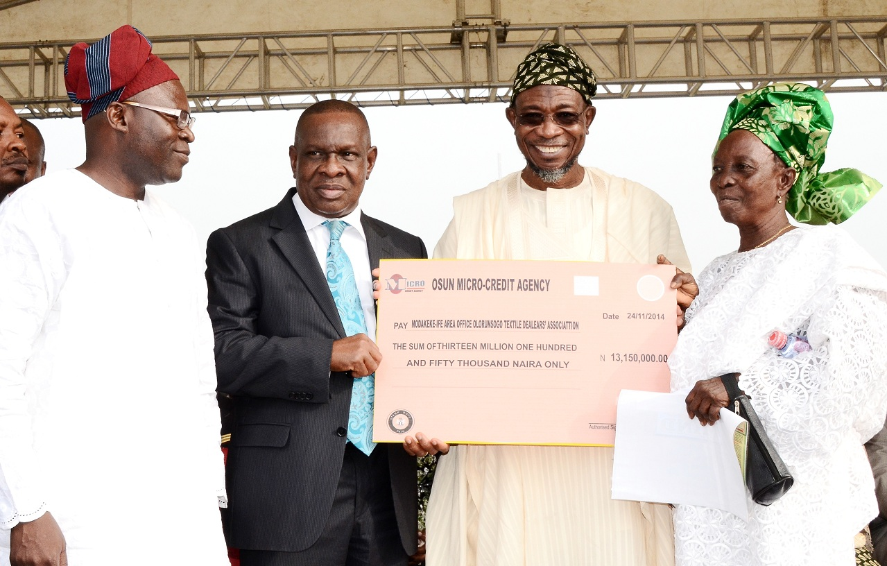 Governor State of Osun, Ogbeni Rauf Aregbesola (right) presenting a cheque to Chairperson, Modakeke-Ife Area Office Olorunsogo Textile Dealers' Association, Mrs Elizabeth Odelola (right), during the Disbursement of N2 Billion Accessed by the State to Loanees under the CBN N220 Billion Micro, Small and Medium Enterprises Development Fund at Nelson Mandela Freedom Park, Osogbo. With them are, Special Adviser to Governor, Central Bank Nigeria (CBN) on Development Finance, Mr Paul Nduka (2nd left) and Commissioner for Commerce, Industry, Cooperatives and Empowerment, Mr Ismaila Alagbada (left) on Monday 24-11-2014