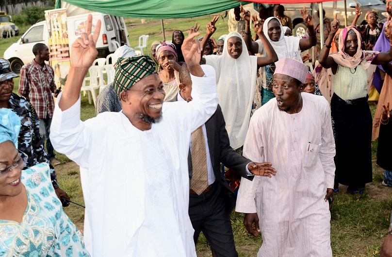 Governor State of Osun, Ogbeni Rauf Aregbesola (2nd left) acknowledging cheers from the Disables and Beggars, during a party organised by them in celebrating Aregbesola's re-election in Osogbo, State of Osun. With him are, his Deputy, Mrs Titi Laoye-Tomori (left); Senior Special Assistant to Governor on Arewa Matters, Imam Bashir Mohammed (3rd left) and others on Friday 07-11-2014