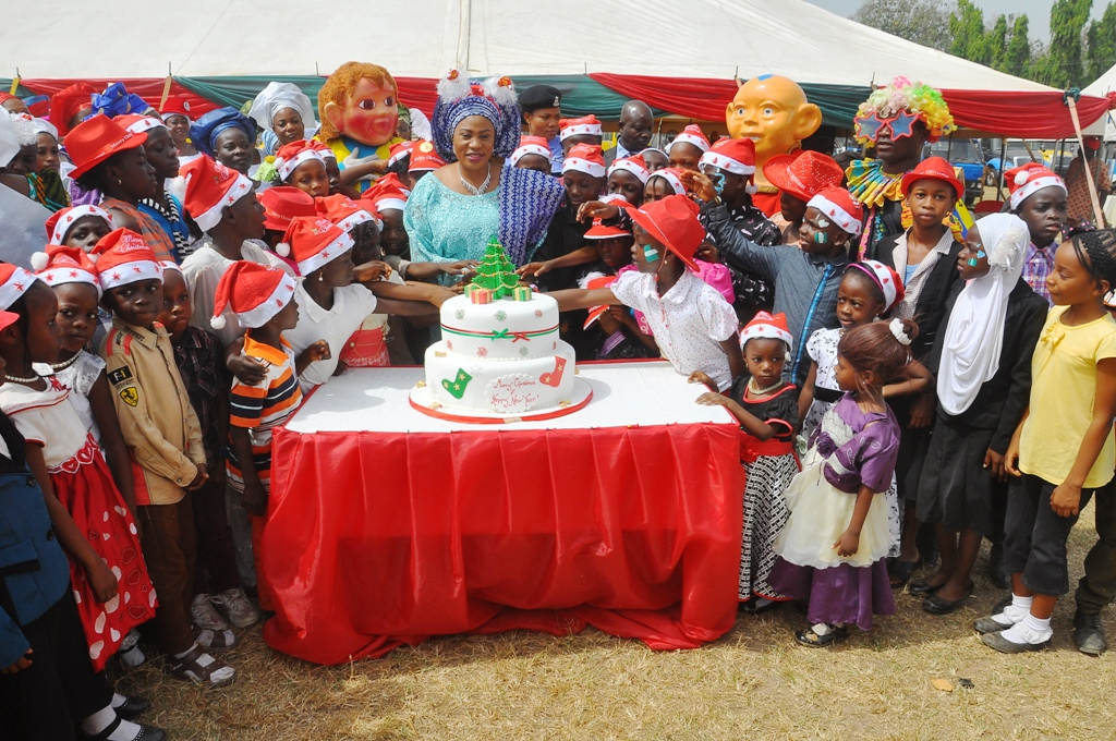 Wife of the State of Osun Governor, Alhaj Sherifat Aregbesola (middle) cutting the anniversary cake with Children, during the 2014 Children End of the Year Party, organised by office of the wife of the Governor in collaboration with Ministry of Women and Children Affairs, at Government House, Osogbo on  Wednesday 17-12-2014