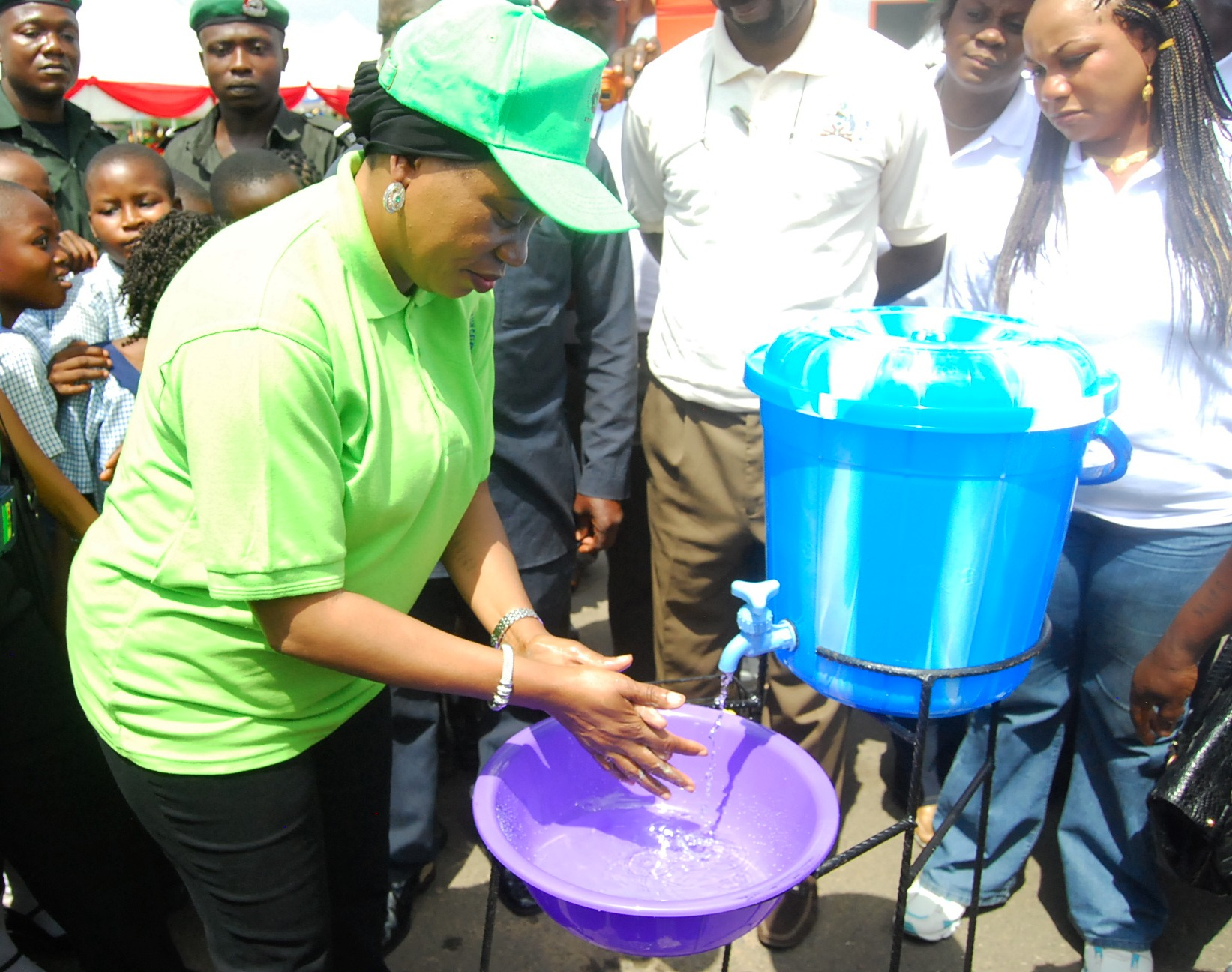 UNICEF Ambassador on Community Led Total Sanitation (CLTS), Mrs Sherifat Aregbesola, demonstrating hand washing. With them are former Special Adviser to Osun Governor on Rural Development and  Community Affairs, Mr kunle Ige and former Commissioner for Environment in Osun, Prof. (Mrs) Olubukola Oyawoye, during the recent 2014 Global hand washing Day celebration in Osogbo, the Sate of Osun.