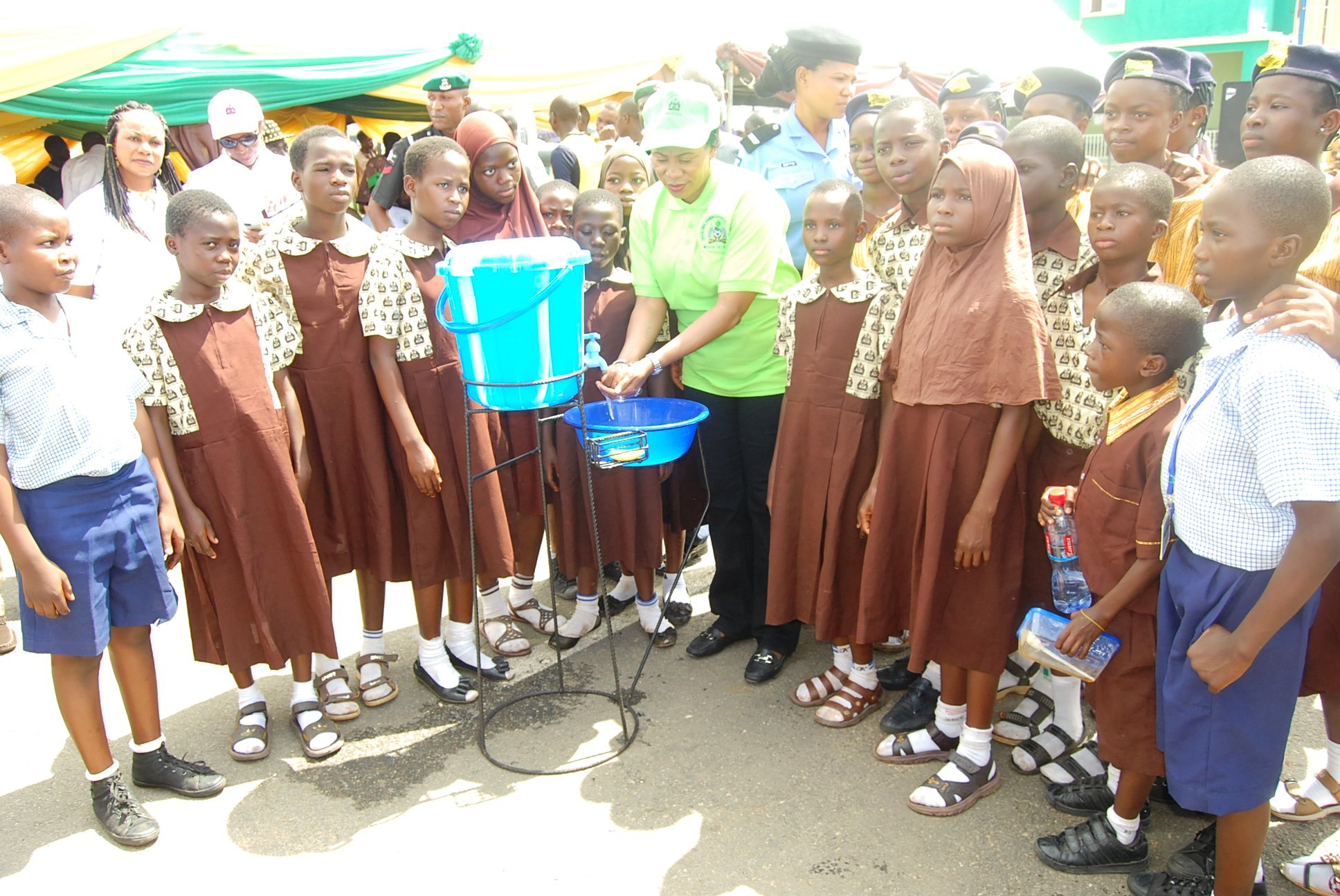 UNICEF Ambassador on Community Led Total Sanitation (CLTS), Mrs Sherifat Aregbesola in a group photograph with students while demonstrating hand washing, during the recent 2014 Global hand washing Day celebration in Osogbo, the Sate of Osun.