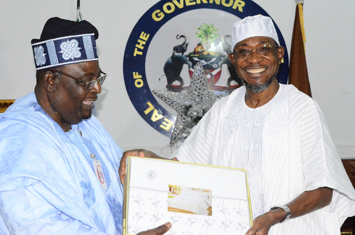 Resident Electoral Commissioner of Independent Electoral Commission (INEC) in Osun, Dr.Rufus Akeju (left), receiving a gift from Governor Rauf Aregbesola of the State of Osun, during a farewell visit at the Government House, Osogbo on Monday 29-12-214