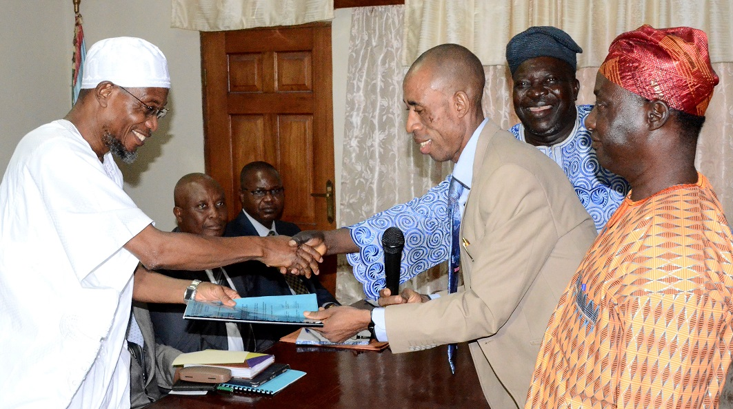Governor State of Osun, Ogbeni Rauf Aregbesola (left) receiving a Report Compiled by Labour on Ways to Improve the State Internal Generated Revenue (IGR) from Chairman, Labour Committee on IGR, Comrade Francis Adetunji (2nd right), during the Official Presentation of the report at Governors' Office, Osogbo, State of Osun. With them are, Chairman, Nigeria Labour Congress (NLC) Osun Chapter, Comrade Saka Adesiyan (left); Chairman, Joint Negotiating Council (JNC) Osun Chapter, Comrade Bayo Adejumo (3rd right) and others