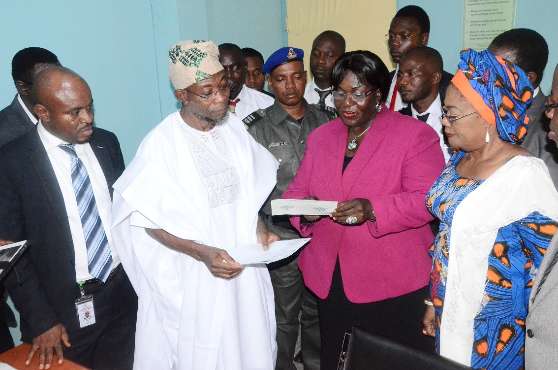 Governor State of Osun, Ogbeni Rauf Aregbesola (2nd left) collecting his National Identification Number from Director Operations, National Identity Management Commission (NIMC) Abuja, Mrs Yahaya Cecilia (2nd right). With them are, Deputy Governor, Mrs Titi Laoye-Tomori (right); State Coordinator, NIMC, Mr Adegoke Kayode (left) and others, at NIMC Registration Centre, Osogbo, the State of Osun