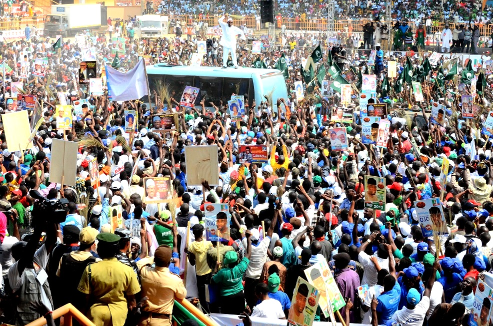 Governor State of Osun, Ogbeni Rauf Aregbesola on the top of a vehicle acknowledging cheers from the broom wielding supporters of the All Progressives Congress APC, during the Presidential Campaign of General Muhammadu Buhari at  Pavilion Central Ado-Ekiti on Saturday 24/01/2015.