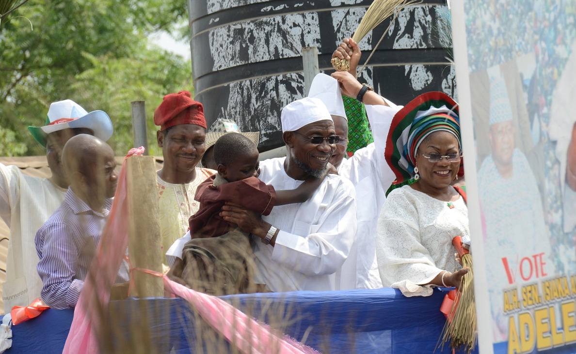 Special passion for APC: Governor State of Osun, Ogbeni Rauf Aregbesola enthusiastically ordered a toddler to the podium after sighting him within a mamoth crowd in his laoud voice shouting APC Shai Buhari; APC Shai Buhari; APC Shai Buhari. With them are, his deputy, Mrs Titi Laoye-Tomori; An Aspirant, Senator Isiaka Adeleke, representing Osun West Senatorial District and others, during a campaign for Gen. Muhammadu Buhari and National Assembly Aspirants, at Palace's Squire, Apomu, State of Osun on Monday 02-02-2014