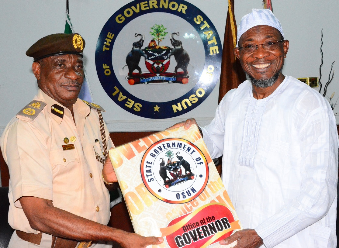 Governor State of Osun, Ogbeni Rauf Aregbesola presenting State Emblem to the Osun State Comptroller of Immigration, Mr. Onunwor Chris, during a Courtesy Visit to the Governor at Government House, Osogbo on Thursday 19/02/2015.