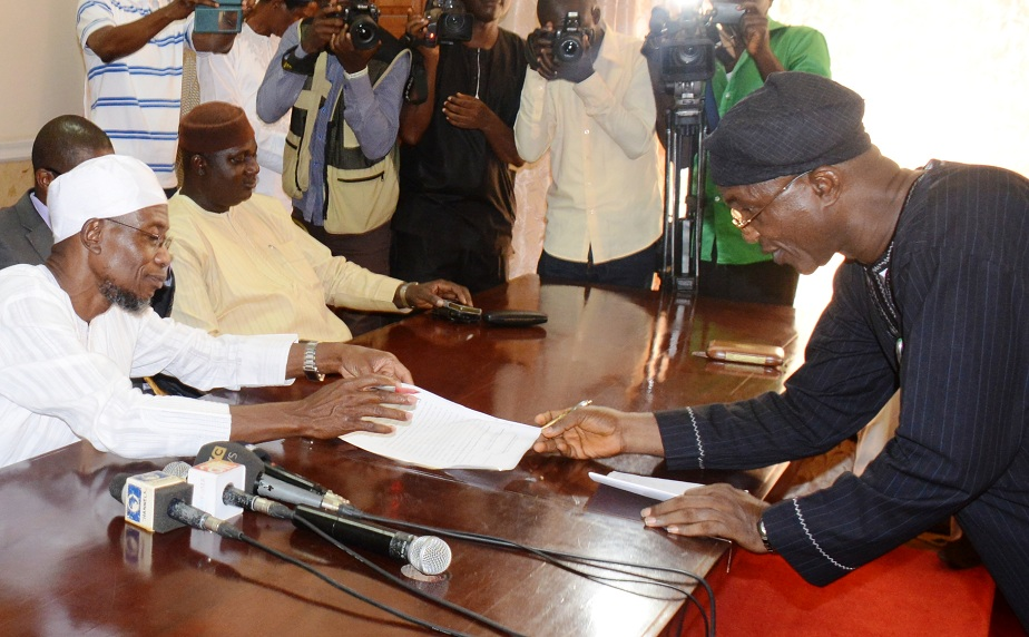 Newly sworn-in Secretary to the State Government of Osun (SSG), Alhaji Moshood Adeoti, signing the oath of office before the Governor State of Osun, Ogbeni Rauf Aregbesola (left) and Former Chairman, All Progressives Congress (APC), Elder Adelowo Adebiyi, during his swearing in Ceremony at Office of the Governor, Osogbo, State of Osun on Wednesday 04-03-2015