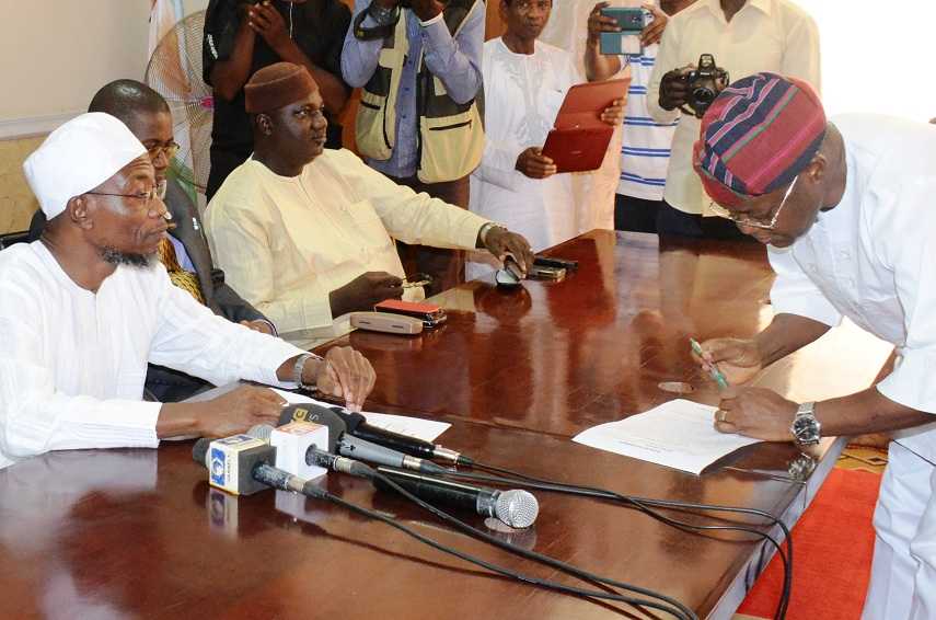 Newly sworn-in Chief of Staff to the Governor (COS), Alhaji Gboyega Oyetola signing the oath of office before the Governor State of Osun, Ogbeni Rauf Aregbesola (left) and Former Chairman, All Progressives Congress (APC), Elder Adelowo Adebiyi, during his swearing in Ceremony at the office of the Governor, Osogbo, State of Osun on Wednesday 04-03-2015