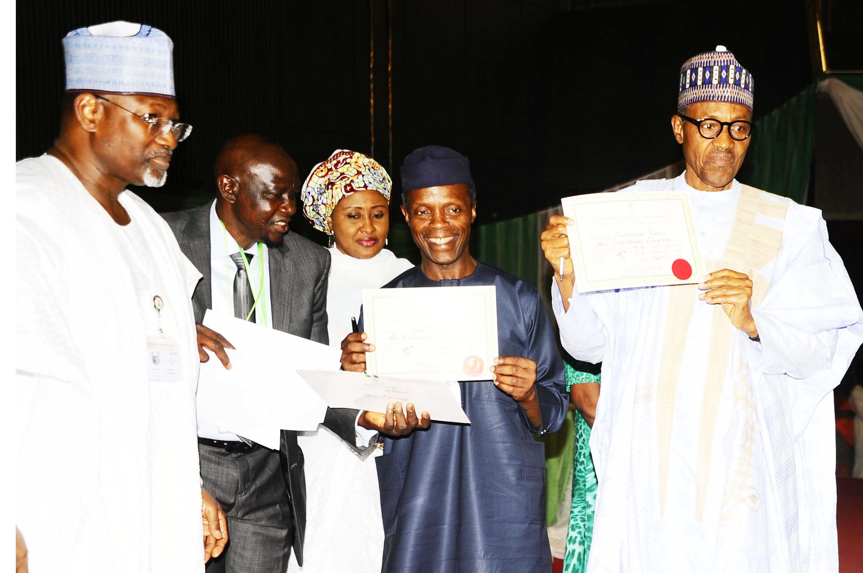 President-Elect, General Muhammadu Buhari (right); his Vice President-Elect, Professor Yemi Osinbajo (2nd right) displaying their Certificates of Return after receiving it from the Chairman, Independent National Electoral Commission (INEC), Professor Attahiru Jega (left) at the National Conference Centre, Abuja on Wednesday 01-04-2015