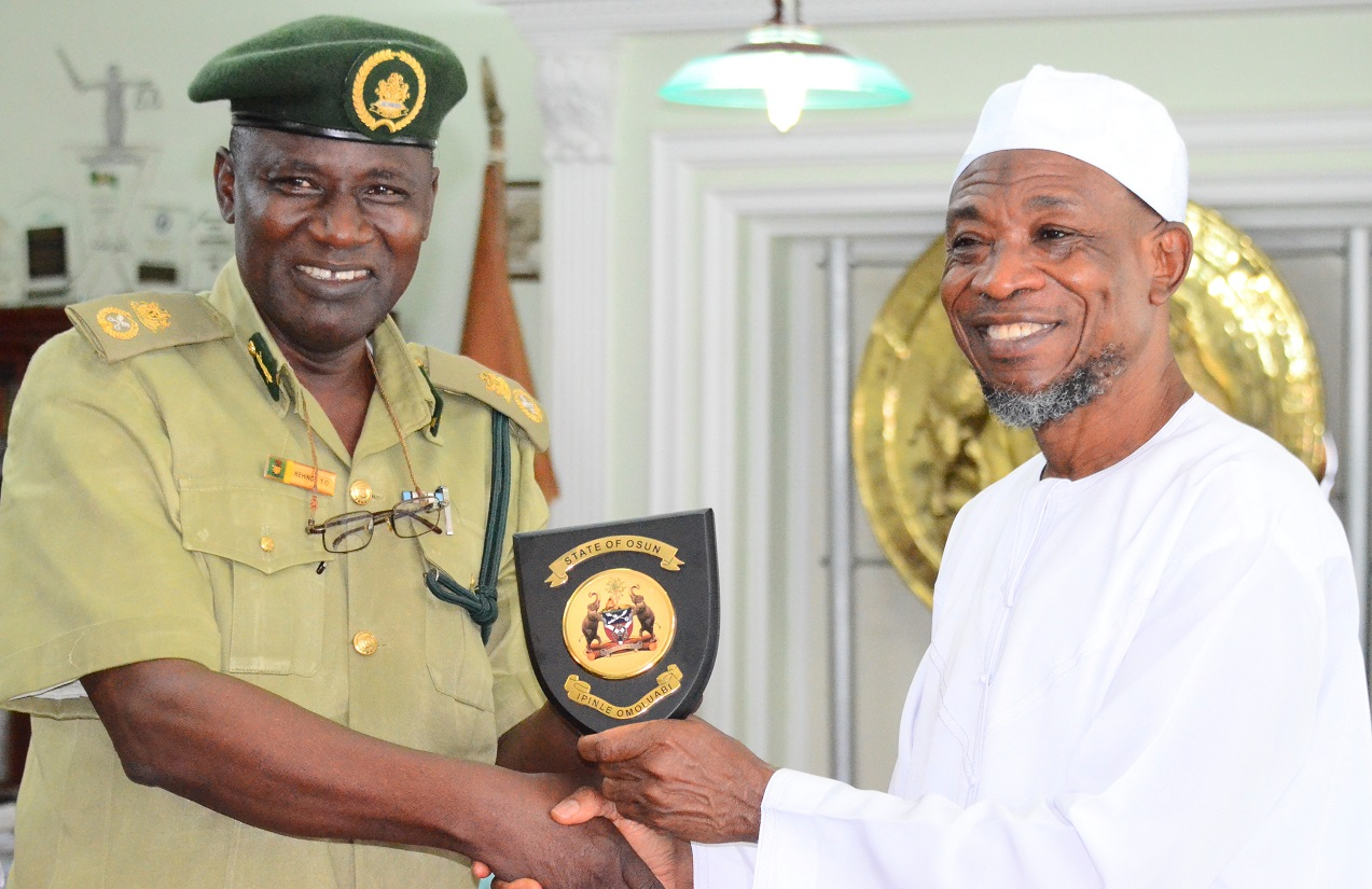 Governor State of Osun, Ogbeni Rauf Aregbesola (right) presenting the State Emblem to the newly posted Controller of Prisons to Osun Command, Mr. Tajudeen Olalekan Kehinde, during a familiarization visit to the Governor in his office at Government Secretariat, Abere, Osogbo on Thursday 13/08/2015.