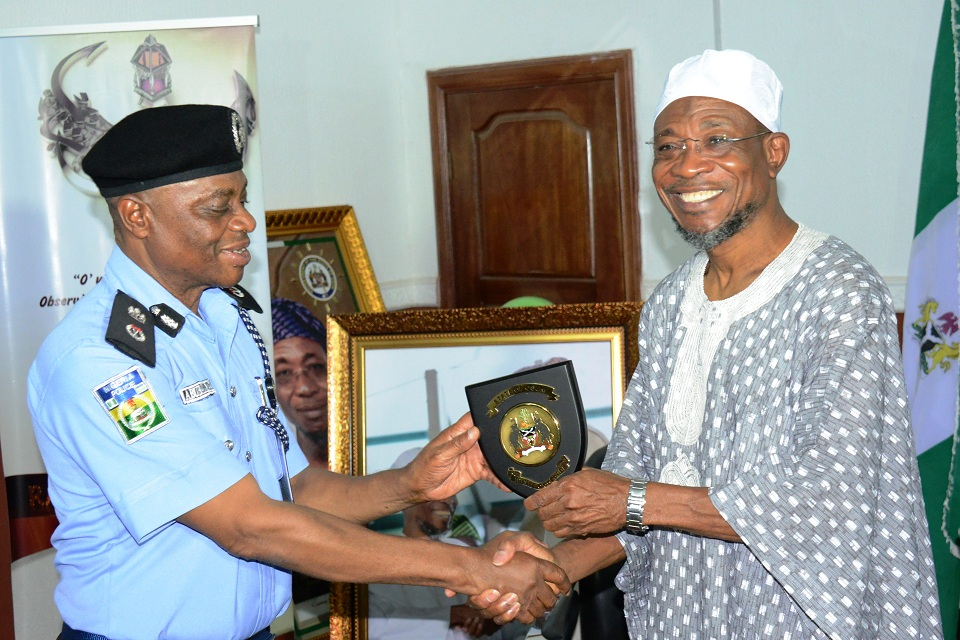 Governor Rauf Aregbesola of Osun, presenting the State plaque to the outgoing Police Commissioner, Mr Abubakar Marafa, during the farewell programme of the outgoing and introduction of the new police commissioner, at the Government House, Osogbo, the State of Osun on Wednesday 02-09-2015