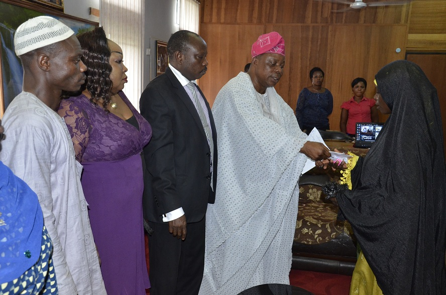 Former Special Adviser to Governor Rauf Aregbesola on Youths, Sports and Special Needs, Comrade Biyi Odunlade, presenting gifts to Mrs. Kafayat Azeez, who has just been rehabilitated by the State Government; her husband, Mr. Azeez Jimoh {left}; Permanent Secretary, Ministry of Youths, Sports and Special Needs, Dr Akinyinka Eso and Director of Special Needs in the Ministry, Mrs Taiwo Oladunjoye,during the handing over ceremony of displaced people to their families after been rehabilitated by Aregbesola's administration, at the Permanent Secretary's office, Government Secretariat, Abere, Osogbo, at the weekend