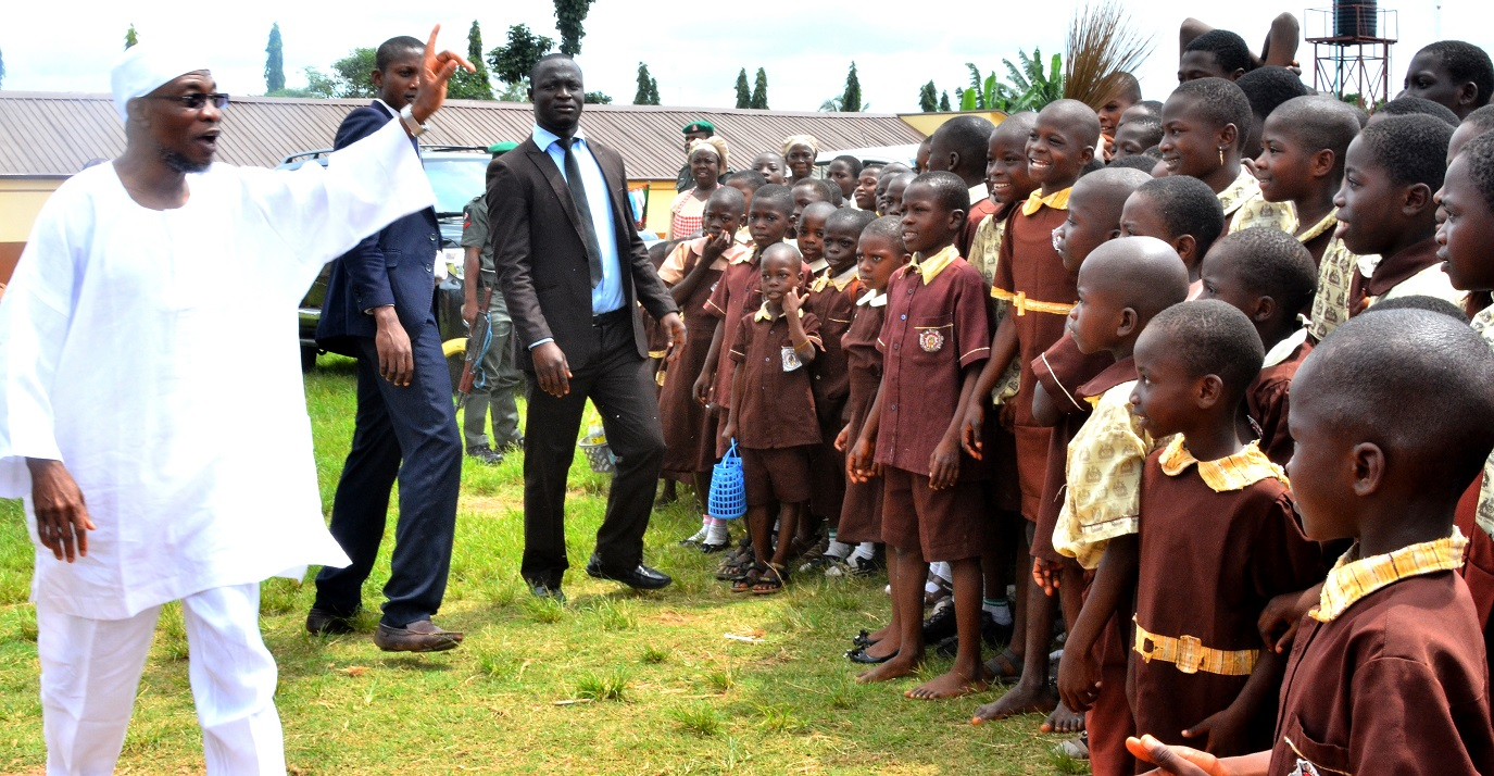Governor State of Osun, Ogbeni Rauf Aregbesola acknowledging cheers from the pupils of Community Elementary/Middle School, Olorunsogo, Dada Estate, during the Inspection Tour to the ongoing construction of the school on Monday 19-10-2015.