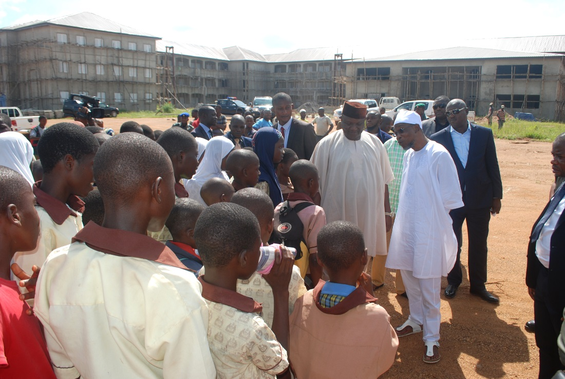 Governor State of Osun, Ogbeni Rauf Aregbesola and Chairman Osun State All Progressive Congress (APC), Prince Gboyega Famodu (right),addressing students, during an inspection visit to the on going Construction of Seventh Day Adventist High School Ede. on Wednesday 4-11-2015.