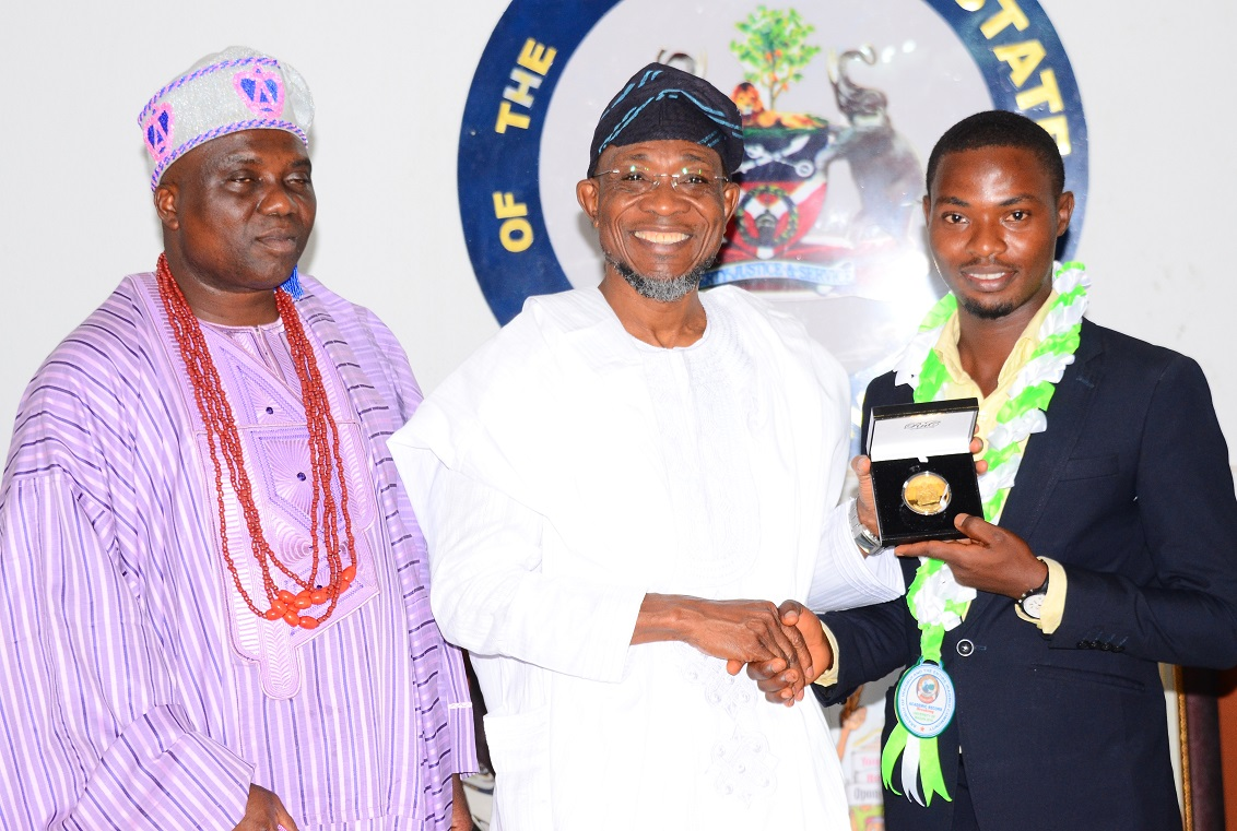 Governor State of Osun, Ogbeni Rauf Aregbesola (middle); presenting an award of excellence to an indigene of Osun who is Overall Best Graduate of the University of Ibadan, Dr. Olayinka Olamide Sodiq (right), as Aragbiji of Iragbiji, Oba Abdul-Rasheed Olabomi watches, during a courtesy call to the Governor, at Government House, Osogbo, State of Osun, on Friday 11-12-2015.