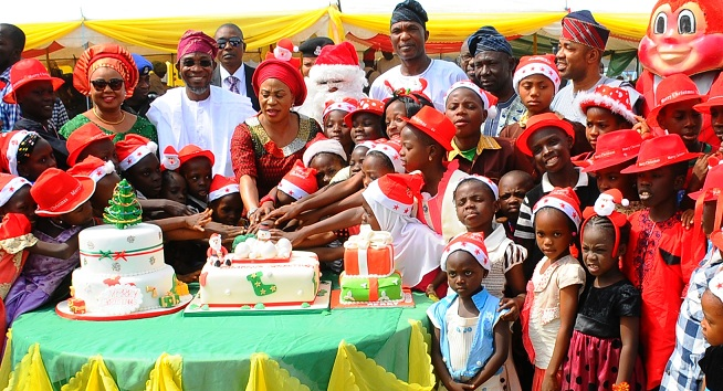 Member of the House of Representative, Alhaja Ayo Omidiran(left), Governor State of Osun, Ogbeni Rauf Aregbesola; his wife, Sherifat; Secretary to the State Government, Alhaji Moshood Adept I and others, cutting cake with children, after the distribution of gifts to children in commemoration of Xmass celebration, organised by Sherifat Aregbesola, at the Government House, Osogbo on Tuesday 22-12-2015