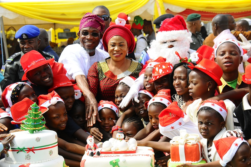 Governor State of Osun, Ogbeni Rauf Aregbesola and his wife, Sherifat (middle), cutting Xmass cake with children after distribution of gifts to them in commemoration of Xmass celebration, organised by wife of the governor at the Government House, Osogbo on Tuesday 22-12-2015