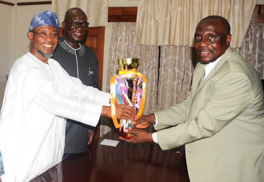 From Left-Governor State of Osun Ogbeni Rauf Aregbesola Receiving the Trophy From the Chairman Osun Football Assosiation, Mr Taiwo Ogunjobi (right); Special Adviser to the governor on Security Matters, Tope Adejumo (2rd left). during the courtesy visit and Presentation of Under 13th Gold Medal, Trophy to the governor by the Osun Under 13th Youth that won the Maiden South West Football Tournament recently in Akure, at the Governor Office Secretariat, Abere, at the weekend