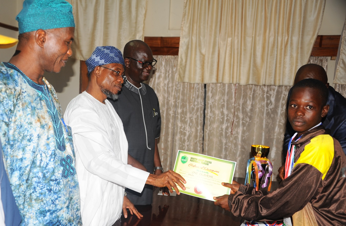 Governor State of Osun Ogbeni Rauf Aregbesola (2nd right) Presenting the Certificate of Participation to Oni Olayemi One of the participant of the Tournament, Secretary to the State Government, Alhaji Moshood Adeoti (left); Special Adviser to the Governor on Security Matters, Tope Adejumo (right), during the courtesy visit and Presentation Certificate of the Under 13th Gold Medal, Trophy to the Governor by Osun Under 13th Youth that won the Maiden South West Football Tournament recently in Akure, at the governor office secretariat Abere on Tuesday 1-12-2015.
