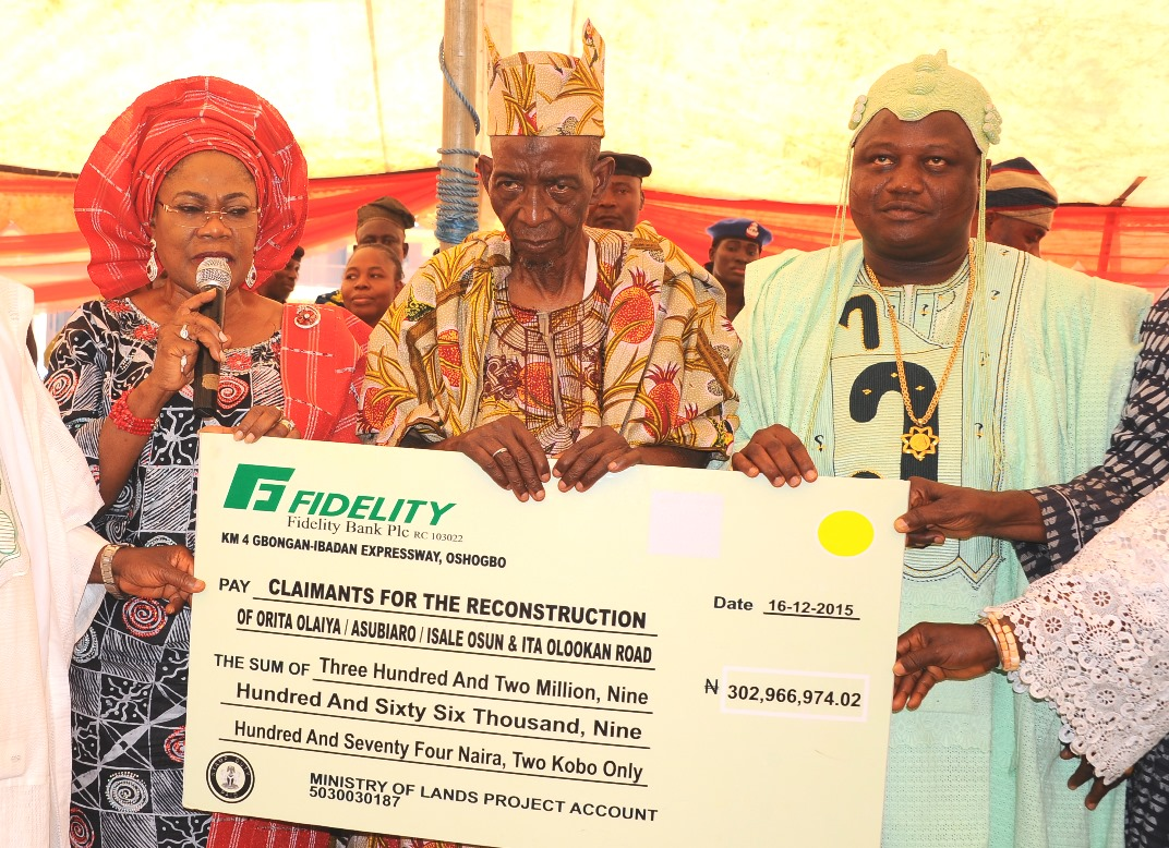 Governor State of Osun, Ogbeni Rauf Aregbesola, Represented by his Deputy, Mrs Titi Laoye-Tomori (left) Presenting the Compensation Check to the Olori Baale Isale-Osun, Chief Saliu Moniade (2nd right). With them is  the Ataoja of Osogbo Land, Oba Jimoh Olanipekun, during the Payment of Compensation to the people affected by the Reconstruction of Orita Olaiya, Asubiaro, Isale-Osun and Ita Olookan Road, Osogbo, at Laro-Timehin Middle School Isale Osun on Wednesday 16-12-2015.