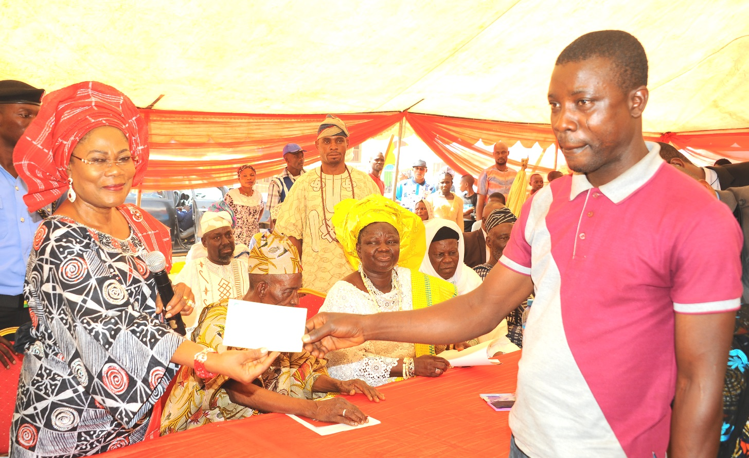 Governor State of Osun, Ogbeni Rauf Aregbesola, Represented by his Deputy, Mrs Titi Laoye-Tomori, presenting the Compensation Check to Mr Busari Saheed, during the Payment of Compensation to the people affected by the Reconstruction of Orita Olaiya, Asubiaro, Isale-Osun and Ita Olookan Road, Osogbo By Ogbeni, at Laro-Timehin Middle School Isale Osun on Wednesday 16-12-2015.